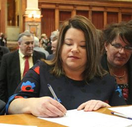 Kirsten signing a document